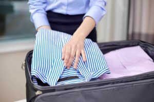 Person folding shirts into suitcase